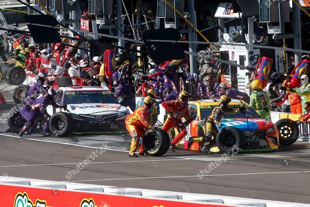 Kyle Busch, right, and Denny Hamlin make pit stops during the NASCAR Cup Series auto race, in Avondale, Ariz