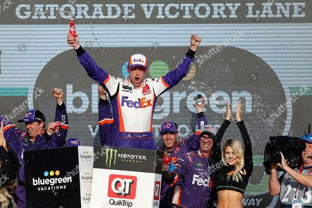 Denny Hamlin celebrates in Victory Lane after winning the NASCAR Cup Series auto race, in Avondale, Ariz