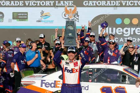 Denny Hamlin. center, holds up the winner's trophy after driving to victory in a NASCAR Cup Series auto race at ISM Raceway, in Avondale, Ariz