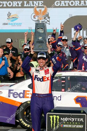 Denny Hamlin holds up the trophy after winning the NASCAR Cup Series auto race, in Avondale, Ariz
