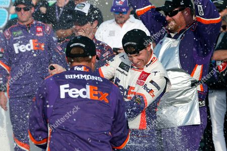 Denny Hamlin, center, gets sprayed with champagne by pit crew members in Victory Lane after he won the NASCAR Cup Series auto race, in Avondale, Ariz