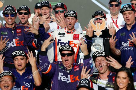 Denny Hamlin, center, and his race team celebrate in Victory Lane after his win in the NASCAR Cup Series auto race Raceway, in Avondale, Ariz