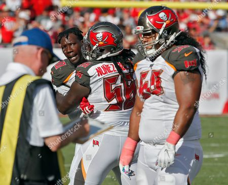 Tampa Bay Buccaneers defensive end Jason Pierre-Paul, let, has to be restrained by defensive tackle Rakeem Nunez-Roches (56) from getting to defensive tackle Vita Vea (50) after an Arizona Cardinals run during the second half of an NFL football game, in Tampa, Fla