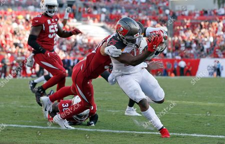 Stock Picture of Tampa Bay Buccaneers running back Peyton Barber (25) slips a tackle by Arizona Cardinals linebacker Joe Walker (59) to score on a 1-yard touchdown run during the second half of an NFL football game, in Tampa, Fla