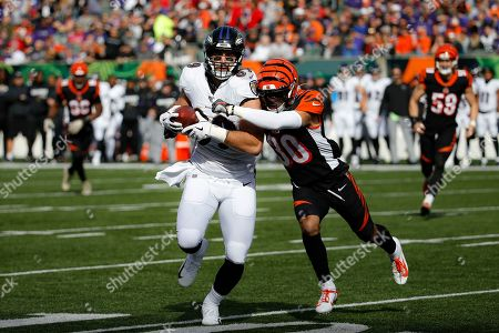 Baltimore Ravens tight end Mark Andrews, left, runs the ball against Cincinnati Bengals free safety Jessie Bates (30) during the first half of NFL football game, in Cincinnati