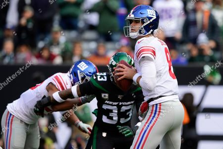 Stock Picture of New York Giants quarterback Daniel Jones (8) looks to pass as New York Jets' Jamal Adams (33) closes in during the first half of an NFL football game, in East Rutherford, N.J. Adams forced a fumble on the play