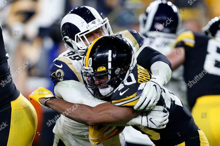 Los Angeles Rams defensive tackle Aaron Donald (99) tackles Pittsburgh Steelers running back Tony Brooks-James (40) during the second half of an NFL football game in Pittsburgh