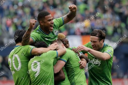 Seattle Sounders defender Roman Torres holds up his arms as he celebrates with teammates after defender Kelvin Leerdam scored a deflected goal against Toronto FC, during the second half of the MLS Cup championship soccer match in Seattle