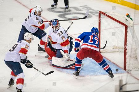 New York Rangers right wing Jesper Fast (17) is unable to score against Florida Panthers goaltender Sam Montembeault (33) as Panthers defensemen Aaron Ekblad (5) and Mike Matheson (19) defend during the third period of an NHL hockey game, in New York