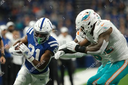 Indianapolis Colts running back Nyheim Hines (21) is pushed out-of-bounds by Miami Dolphins middle linebacker Raekwon McMillan (52) during the first half of an NFL football game in Indianapolis