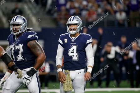 Stock Image of Dallas Cowboys' Dak Prescott (4) and Tyron Smith (77) watch play in the second half of an NFL football game against the Minnesota Vikings in Arlington, Texas