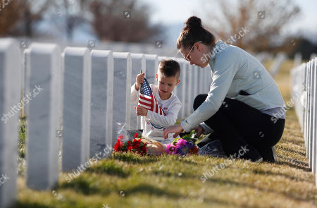 Caleb, Lyuba Vester. Caleb Vester, left, helps his mother, Lyuba, to place flags and flowers at the gravesite of his father, James Thomas Vester, who served in the Persian Gulf War, to mark the Veterans Day holiday in Fort Logan National Cemetery, in Sheridan, Colo