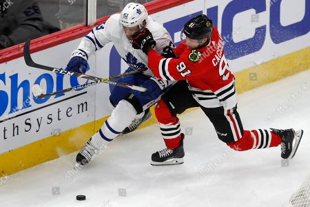 Chicago Blackhawks' Drake Caggiula, right, checks Toronto Maple Leafs' Cody Ceci during the third period of an NHL hockey game, in Chicago