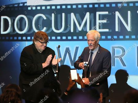 Stock Photo of Michael Moore, Michael Apted. Winner of last years's Critic's Choice Lifetime Achievement Award, Michael Moore, applauds after presenting Michael Apted with the Landmark Award at the Fourth Annual Critics' Choice Documentary Awards in New York, N.Y