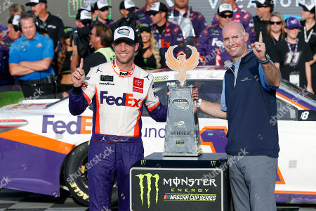 Stock Image of Denny Hamlin, left, and Shawn Pearson, President and CEO of Bluegreen Vacations, stand with the winners trophy in victory lane following the NASCAR Cup Series auto race at ISM Raceway, in Avondale, Ariz
