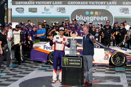 Denny Hamlin, left, and Shawn Pearson, President and CEO of Bluegreen Vacations, stand with the winners trophy in victory lane following the NASCAR Cup Series auto race at ISM Raceway, in Avondale, Ariz