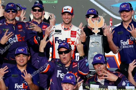 Denny Hamlin, center, and his race team in victory lane after winning the NASCAR Cup Series auto race at ISM Raceway, in Avondale, Ariz