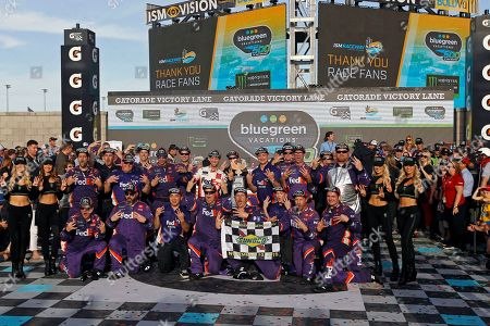 Denny Hamlin and his race team in victory lane after winning the NASCAR Cup Series auto race at ISM Raceway, in Avondale, Ariz
