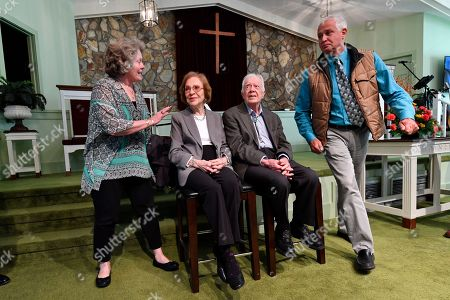 Former President Jimmy Carter, second from right, and former first lady Rosalynn Carter sit, as guests Romona Kluth, left, and husband Doug Kluth, from Nebraska, finish their turn of having their photo made with them, after Sunday school at Maranatha Baptist Church, in Plains, Ga