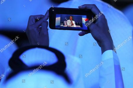 An Emirati man takes video of former US Secretary of State, Condoleezza Rice on his mobil phone at the opening ceremony of the Abu Dhabi International Petroleum Exhibition & Conference, ADIPEC, in Abu Dhabi, United Arab Emirates
