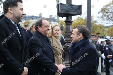 French President Emmanuel Macron (R) shakes hands with former French president Francois Hollande (C), next to French National Assembly vice-president Hugues Renson (L), during a ceremony at the Arc de Triomphe in Paris, France, 11 November 2019, as part of the commemorations marking the 101st anniversary of the 11 November 1918 armistice, ending World War I (WWI).