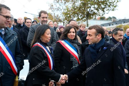 French President Emmanuel Macron shakes hands with Paris 8th arrondissement mayor Jeanne d'Hauteserre, second left, next to Paris mayor Anne Hidalgo and 17th arrondissement mayor Geoffroy Boulard, left, during commemorations marking the 101st anniversary of the 1918 armistice, ending World War I