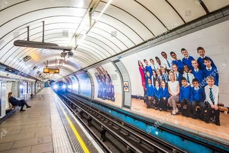 Stock Image of Yr 3 project posters on the platform billboards at Pimlico underground station - Steve McQueen's Year 3 project can now be seen as a large-scale installation at in the Duveen Galleries at Tate Britain. It is also on 600 billboards across all 33 of London's boroughs. The images feature class photos of Year 3 school children from London primary schools. The billboards are on high streets, railway platforms, roadside sites, and underground stations until mid-November