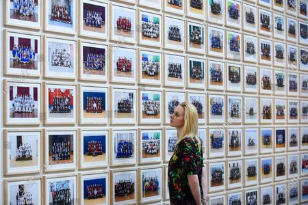 """Stock Picture of A staff member views works at the preview of """"Year 3"""", an exhibition by Turner Prize-winning artist and Oscar-winning filmmaker Steve McQueen at Tate Britain.  The artwork comprises 3,128 traditional school class photographs of Year 3 pupils from 1,504 of London's primary schools.  The work reflects a picture of the present and is on display 12 November to 3 May 2020."""