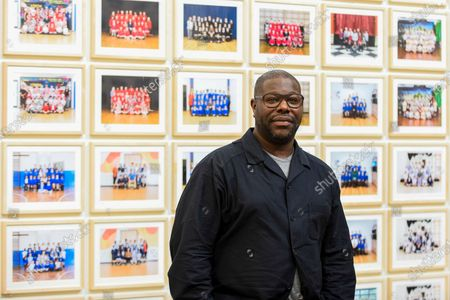 """Stock Photo of Turner Prize-winning artist and Oscar-winning filmmaker Steve McQueen poses at the preview of """"Year 3"""", his new exhibition at Tate Britain.  The artwork comprises 3,128 traditional school class photographs of Year 3 pupils from 1,504 of London's primary schools.  The work reflects a picture of the present and is on display 12 November to 3 May 2020."""