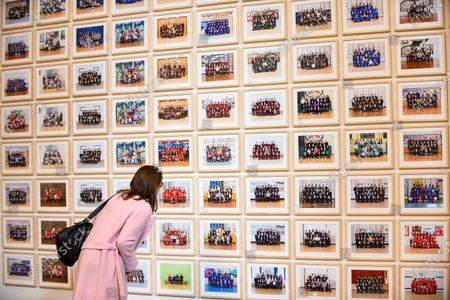 """A visitor views works at the preview of """"Year 3"""", an exhibition by Turner Prize-winning artist and Oscar-winning filmmaker Steve McQueen at Tate Britain.  The artwork comprises 3,128 traditional school class photographs of Year 3 pupils from 1,504 of London's primary schools.  The work reflects a picture of the present and is on display 12 November to 3 May 2020."""