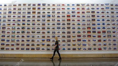 """A staff member walks by works at the preview of """"Year 3"""", an exhibition by Turner Prize-winning artist and Oscar-winning filmmaker Steve McQueen at Tate Britain.  The artwork comprises 3,128 traditional school class photographs of Year 3 pupils from 1,504 of London's primary schools.  The work reflects a picture of the present and is on display 12 November to 3 May 2020."""