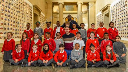 """Turner Prize-winning artist and Oscar-winning filmmaker Steve McQueen poses with staff and pupils from Tyssen Community School from Hackney at the preview of """"Year 3"""", his new exhibition at Tate Britain.  The artwork comprises 3,128 traditional school class photographs of Year 3 pupils from 1,504 of London's primary schools.  The work reflects a picture of the present and is on display 12 November to 3 May 2020."""