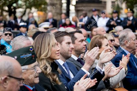 Eric Trump, the son of President Donald Trump, and his wife Lara Yunaska Trump, center applaud as President Donald Trump and first lady Melania Trump participate in a wreath laying ceremony at the New York City Veterans Day Parade at Madison Square Park, in Washington
