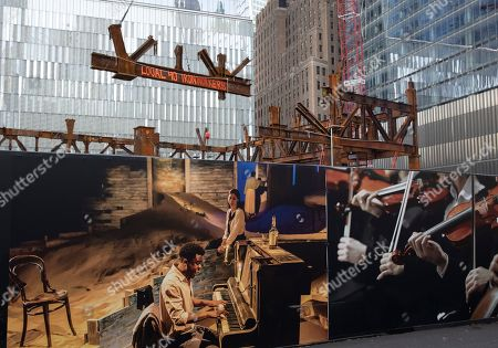 Pieces of structural steel are hoisted by crane to the The Ronald O. Perelman Performing Arts Center under construction, in New York. The multi-space 800-seat center is part of the World Trade Center complex. In the foreground photographic murals cover the construction site wall