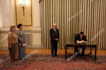 Chinese President Xi Jinping (R) signs the guest book in the presence of Greek President Prokopis Pavlopoulos (C) and their spouses Chinese First Lady Peng Liyuan (2-L) and Greek First Lady Vlassia Pavlopoulou-Peltsemi (L) before a formal dinner at the Presidential Palace in Athens, Greece, 11 November 2019. The Chinese President is paying a two-day official visit to Greece.
