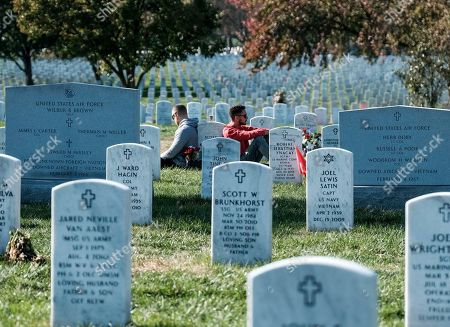 Tony Brown, left, and Neil Thomas pay respects at a friends' grave on Veteran's Day at the Arlington National Cemetery, in Arlington, Virginia on