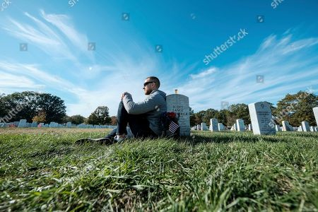 Tony Brown pays respects at friends' grave on Veteran's Day at the Arlington National Cemetery, in Arlington, Virginia on