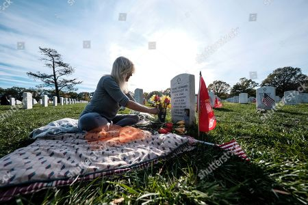 Christine Honeycutt places flowers on the grave of her son Terry Honeycutt Jr. on Veteran's Day at the Arlington National Cemetery, in Arlington, Virginia on . (AP Photo/Michael A. McCoy
