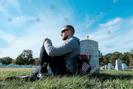 Tony Brown pays respects at friends grave on Veteran's Day at the Arlington National Cemetery, in Arlington, Va. on