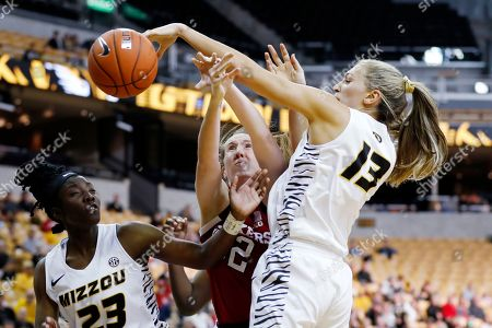 Missouri guard Amber Smith (23) and forward Hannah Schuchts (13) double team Nebraska forward Leigha Brown (32) as they battle for a rebound during an NCAA women's basketball game, in Columbia, Mo