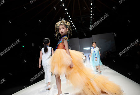 Chinese child model Chen Ruo Xi (C) walks on the runway walk on the runway during a rehearsal before the local kids wear brand Van Monfe show in the China Fashion Week Kids Fashion segment at the 751 Tank venue in Beijing, China, 01 November 2019. More than 60 children and their parents are already gathered at the 751 Tank venue for a rehearsal of the runway show for kids fashion brand, Van Monfe. It is just one of the 35 shows dedicated to kids fashion during the China Fashion Week running from 25 October to 02 November 2019. There are a total of 94 runway shows featuring mostly local brands at the 751 D Park complex during the week. The kids wear market, worth 209.1 billion RMB (26.76 billion euros) in 2018 according to Euromontior, is one of the fastest growing industry in China, partly due to the full implementation of the two-child policy in 2016. This along with the influence of social media, has spurred greater demand for child models and brought about a boom in the industry with many modeling schools catering to children springing up all over the country.  New Silk Road, a modeling agency and school with branches in Beijing and various cities in China, offers modeling classes to children aged 4 to 14 years old at three different levels. The classes are normally held during the weekends, each class lasting two hours. The students can opt for six-months, one-year or two-year courses with fees ranging from 7800 to 24,000 RMB (about 1000 to 3000 euros) where they learn how to walk and pose on the catwalk. The school also offers opportunities for the young students to participate in competitions and fashion shows.