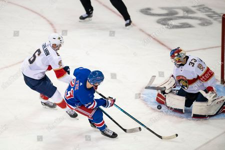 Florida Panthers goaltender Sam Montembeault (33) stops a puck shot by New York Rangers defenseman Adam Fox (23) as Florida Panthers Anton Stralman (6) defends during the third period of an NHL hockey game, in New York. The Panthers go on to win 6-5 in a shootout