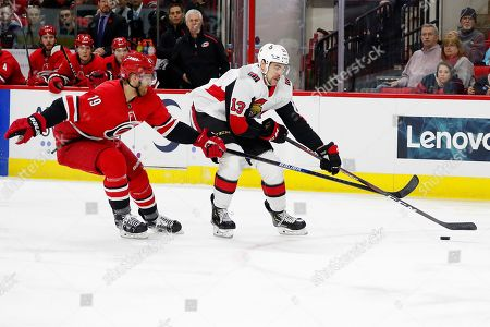 Dougie Hamilton, Nick Paul. Carolina Hurricanes' Dougie Hamilton (19) slows down Ottawa Senators' Nick Paul (13) during the first period of an NHL hockey game in Raleigh, N.C