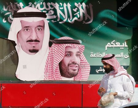A man carries his food as he walks past a banner showing Saudi King Salman, left, and Crown Prince Mohammed bin Salman, in Jiddah, Saudi Arabia