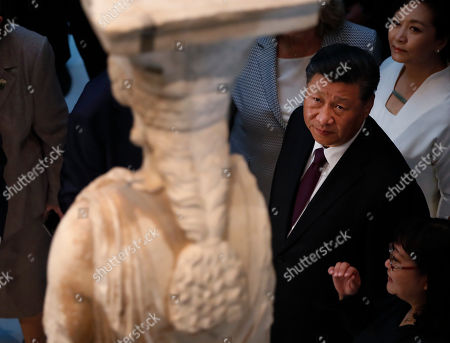 China's President Xi Jinping loos at a 2,500-year-old Caryatid statue, during a visit at the Acropolis Museum, part of his two-day official visit to Greece, in Athens