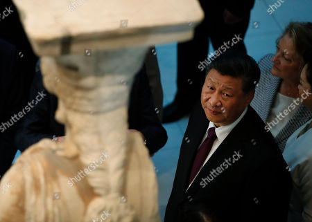 China's President Xi Jinping looks at a 2,500-year-old Caryatid statue, during a visit at the Acropolis Museum, part of his two-day official visit to Greece, in Athens