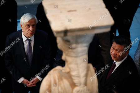 China's President Xi Jinping, right, accompanied by his Greek counterpart Prokopis Pavlopoulos, left, look at a 2,500-year-old Caryatid statue, during a visit at the Acropolis Museum, part of the Chinese President's two-day official visit to Greece, in Athens