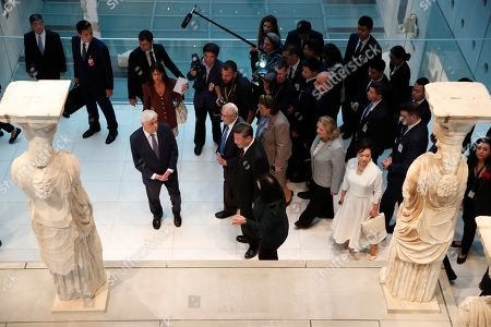 China's President Xi Jinping, centre, accompanied by his Greek counterpart Prokopis Pavlopoulos, left, walk by the 2,500-year-old Caryatid statue, during a visit at the Acropolis Museum, part of the Chinese President's two-day official visit to Greece, in Athens