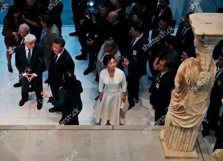 China's President Xi Jinping, centre, accompanied by his Greek counterpart Prokopis Pavlopoulos, left, walk by the 2,500-year-old Caryatid statue, as Chinese president's wife Peng Liyuan, white dress looks at one of them, during a visit at the Acropolis Museum, part of the Chinese President's two-day official visit to Greece, in Athens