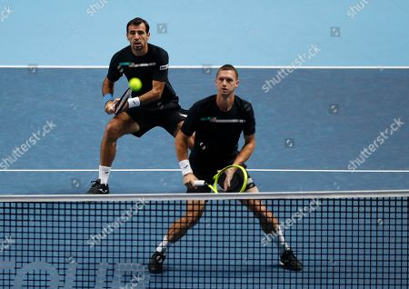 Stock Picture of Ivan Dodig of Croatia, left, and Filip Polasek of Slovakia play a return to Rajeev Ram of the United States and Joe Salisbury of Britain during their ATP World Tour Finals doubles tennis match at the O2 Arena in London